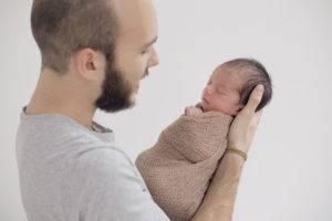 newborn estudio padre enrollado
